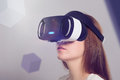Woman in VR headset looking up at the objects in virtual reality Royalty Free Stock Photo