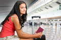 Woman waiting in an airport young at holding tickets Royalty Free Stock Image