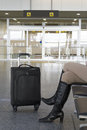 Woman waiting at the arrivals gate of an airport sitting with her suitcase Stock Image
