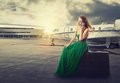 Woman waiting flight departure sitting on suitcase talking on phone beautiful for mobile with airplane background Royalty Free Stock Images