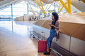 Woman waiting her flight using mobile phone at the airport Royalty Free Stock Photo