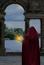 Woman waiting by lake with lantern wearing red cape Royalty Free Stock Image