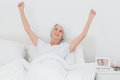 Woman waking up and raising arms in bed mature Royalty Free Stock Photos