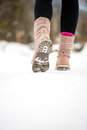 Woman walking away from the camera through winter snow Royalty Free Stock Photo