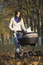 Woman walking with baby in pram at park full length of a young women Royalty Free Stock Image