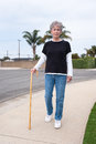 Woman walking with cane Royalty Free Stock Photos
