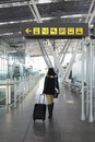 Woman walking through a corridor of an airport photograph with her suitcase hall Stock Image