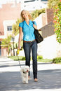 Woman walking with dog in city street Stock Photos