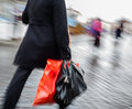 Woman walking down the street in the rain with a red package abstract image of and black bag Royalty Free Stock Image