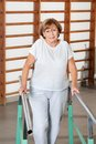 Woman walking with the help of support bars portrait a happy senior at hospital gym Royalty Free Stock Photo