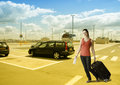 Woman walking with her suitcase at the car parking place young pretty smiling by street and travel ticket ready for holiday Stock Image