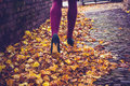 Woman walking through leaves in purple leggings and high heels is on an autumn day Stock Photos