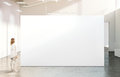 Woman walking near blank white wall mockup in modern gallery Royalty Free Stock Photo