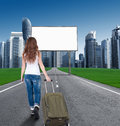 Woman walking on the road to the city in front of an empty bill billboards concept tourist returns home moving Stock Photos
