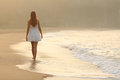 Woman walking on the sand of the beach back view a at sunset Royalty Free Stock Photo