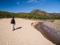 Woman walking on the sand near a river in acadia national park Stock Images