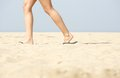 Woman walking in sandals on sand side view at the beach Royalty Free Stock Images