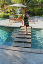 Woman walking on steps across pool Royalty Free Stock Photo