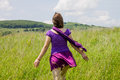 Woman walking in the sunny meadow on summer day touching grass Stock Images