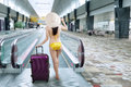 Woman walking to escalator wearing bikini Royalty Free Stock Photo