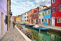 Woman walks in Burano island picturesque street with small colored houses in row, water canal with fishermans boats, c