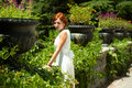 Woman walks in the lush garden at summer day Stock Photography