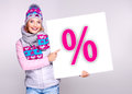 Woman in warm outerwear holds the banner with perсent symbol adult smiling white on it Royalty Free Stock Images