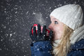 Woman warming up with hot drink in snow Stock Images