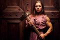 Woman warrior with axe standing at the door Royalty Free Stock Photography