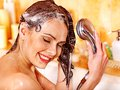 Woman washes her head at bathroom. Royalty Free Stock Image