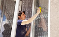Woman washes a window pane young in blue shirt Stock Images