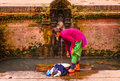 A woman washing clothes in bhaktapur neplease is traditionally an ancient tap of nepal Stock Photo