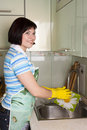 Woman washing dishes in kitchen Stock Image