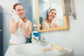 Woman washing her face with clean water in bathroom morning hygiene cleaning Stock Photos