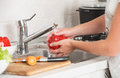 Woman washing vegetables red pepper under the tap Royalty Free Stock Photo
