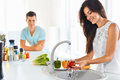 Woman washing vegetables in the sink and man standing next to he Royalty Free Stock Photo