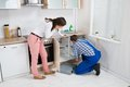 Woman Watching As Worker Repairing Sink Pipe Royalty Free Stock Photo