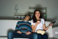 Woman watching television at home with enthusiasm her husband is sleeping next to the couch Royalty Free Stock Photo