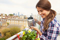 Woman watering plant in container on rooftop garden Royalty Free Stock Photos