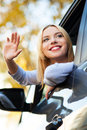 Woman waving from car window Royalty Free Stock Image