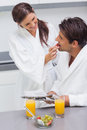 Woman wearing bathrobe feeding her husband strawberry in kitchen Royalty Free Stock Images