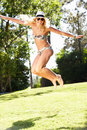 Woman Wearing Bikini Jumping In Garden Stock Images