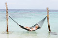 Woman wearing bikini and sun hat relaxing in beach hammock asleep Stock Images