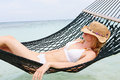 Woman wearing bikini and sun hat relaxing in beach hammock asleep Stock Photography