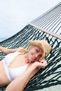 Woman wearing bikini and sun hat relaxing in beach hammock smiling to camera Stock Image