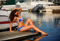 Woman wearing bikini and sunglasses relaxing on the pier sexy brunette attractive girl enjoying bright sun shine in yacht port Stock Images