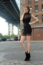 Woman wearing black minidress standing under manhattan bridge young at dumbo area in brooklyn ny Royalty Free Stock Image