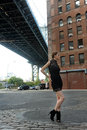 Woman wearing black minidress standing under manhattan bridge young at dumbo area in brooklyn ny Stock Photography