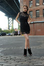 Woman wearing black minidress standing under manhattan bridge young at dumbo area in brooklyn ny Stock Images