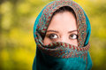 Woman wearing blue, grey and brown coloured scarf covering face only revealing beautiful green eyes, garden background Royalty Free Stock Photo